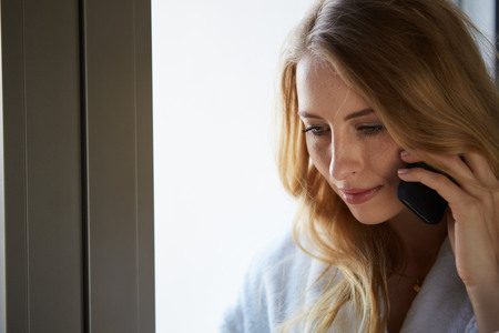 Photo pour Young businesswoman talking on mobile phone while standing by window in office. Beautiful young female model in bright office. - image libre de droit