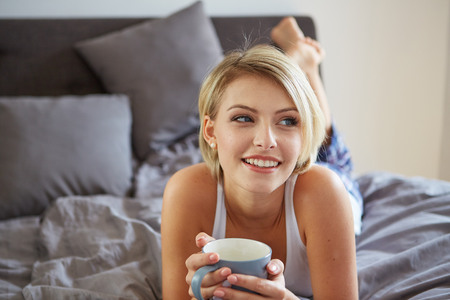 Happy smiling beautiful blond woman awaking with cup of coffee at bedroom