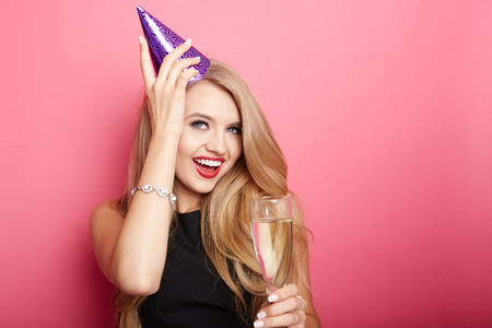 Young celebrating woman black dress, holding a glass of champagne.