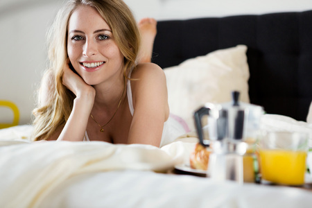Photo for a beautiful woman having breakfast in bed - Royalty Free Image