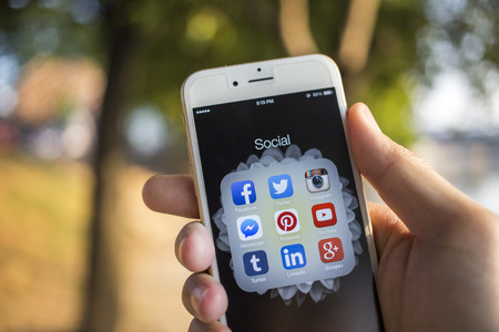 Photo for CHIANG MAI, THAILAND - JANUARY 04, 2015: All of popular social media icons on smartphone device screen with hand holding on Apple iPhone 6. - Royalty Free Image