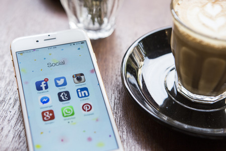 Photo pour CHIANG MAI, THAILAND - APRIL 22, 2015: All of popular social media icons on smartphone device screen Apple iPhone 6 on coffee table. - image libre de droit