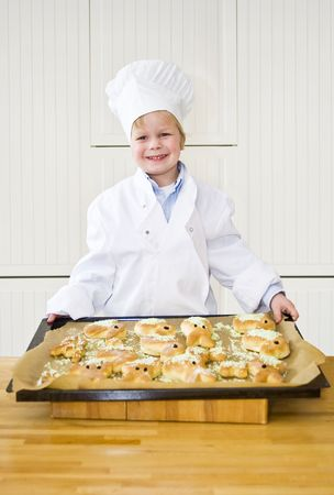 A proudly looking boy, dressed as a chef, showing the easter bunny shaped breads he has baked