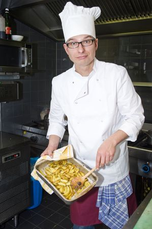 A chef proudly showing a tray of fried potatoes