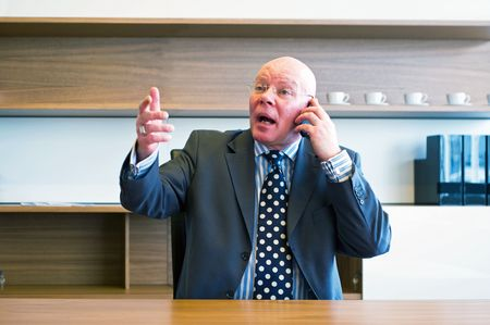 Senior executive wildly gesturing in frustration, taliking on the phone