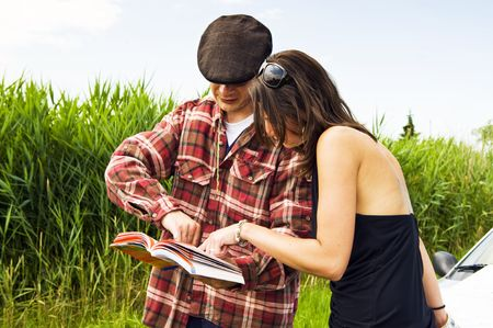 Young woman asking a farmer for advice on where to go, consulting a guide book