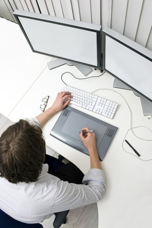 A designer working behind two monitors, using a keyboard and a graphic tablet