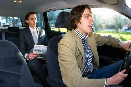 A businessman in the backseat of a taxi