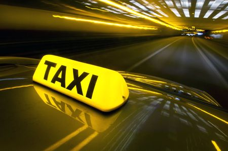 A cab at high speed on a motorway in an urban area with the lit taxi sign on top of its roof