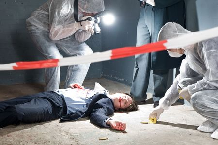 Murder scene with two forensic analysts and a police lieutenant investigating a crime on a businessman in a basementMurder scene with two forensic analysts and a police lieutenant investigating a crime on a businessman in a basement