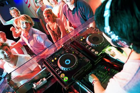 Group of dancing people in front of a dj in a discotheque