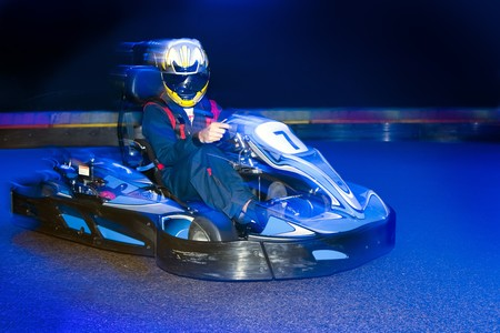 Go-cart driver during a lap on an indoor carting circuit