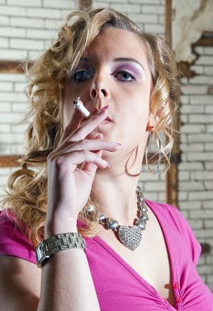 Vain, over the top dressed woman smoking a cigarette, and looking arrogant