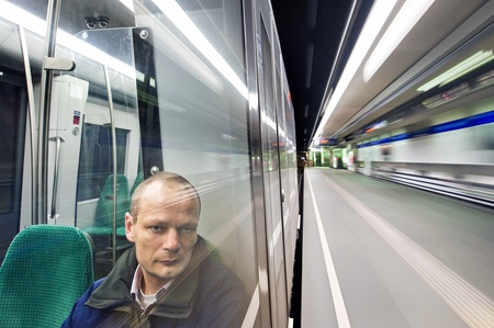 Man, sitting in a metro at night, passing a station, looking out the window with a weary  and tired look in his eyes