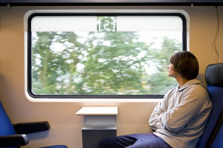 Young man looking out of the window of a train on a grey, rainy day