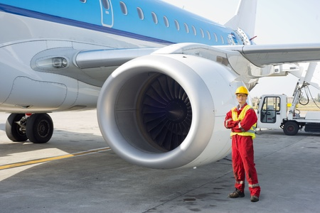 Jet engine mechanic posing next to a commercial aircraft on the runway