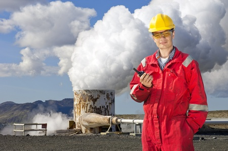 Engineer with cb radio standing next to the violently emitting tube of a geothermical energy plant