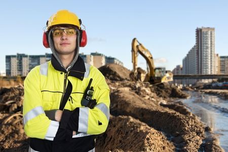 Young construction engineer posing in front of the muddty construction site of a large building project