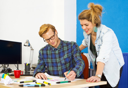 Two creative designers, working on a product innovation, developing ideas and brainstorming together behind a desk in a design studio