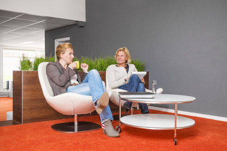 Coworkers sitting down for a good conversation with coffee in an inspiring office environment discussing their assignment