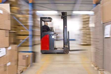 Reach truck forklift driving past an isle in a warehouse at speed. A panned image, with stock and cardboard boxes in the shelfs of the storage racks. Conceptual image about internal logistics, shipping and delivery, distribution and handling of various su