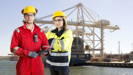 Two dockers, wearing safety gear, protection and work clothing, posing in front of a large container ship in an industrial harbor
