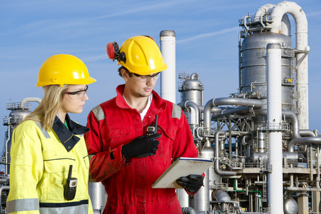 Photo pour Two engineers going through routine checks, working at a petrochemical oil refinery using cb radios and a tablet computer - image libre de droit