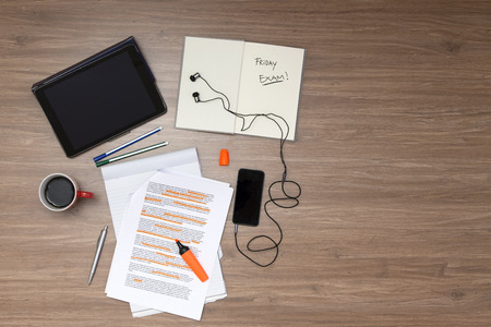 Background, filled with studying materials and copy space on a wooden surface. Items include an electronic tablet, music player, text book, cup of coffee, pens, markers, a high lighted standard (lorum ipsum) text, seen from above