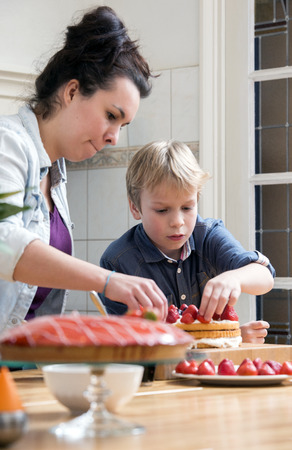 Au Pair and son topping strawberries on cake in kitchen