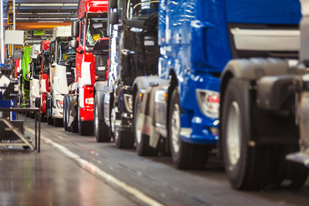 Photo for Row of brand new, shiny, trucks in various colours, ready to come off a production line in a truck factory - Royalty Free Image