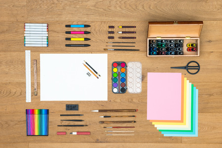 Assorted array of arts, crafts, drawing and design items, such as pens, rulers, markers, felt tip pens, fountain pens brushes, watercolor, and various sheets of paper on a wooden surface