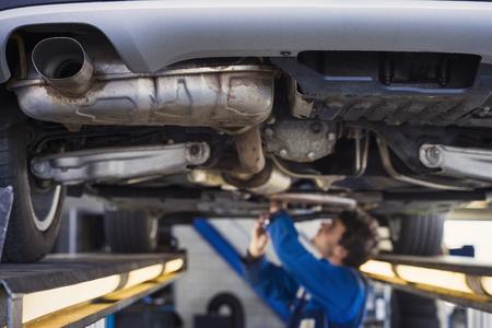 Photo pour Exhaust of a car on the bridge at a auto repair shop with a mechanic underneath - image libre de droit