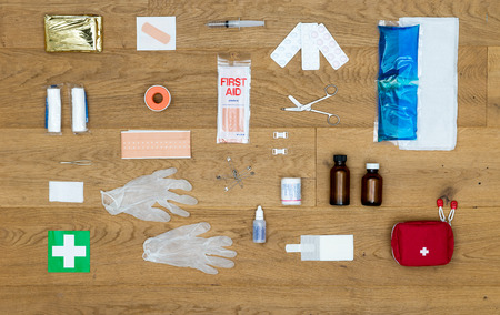 The items and objects in a first aid kit, neatly aligned on a wooden surface, including pliers, bandages, plaster, pills, heat or cold pack, isolation blanket, tape, rubber gloves, safety pins and much more.