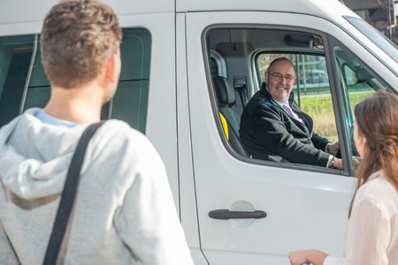 Photo for Smiling professional driver in van looking at passengers at airport - Royalty Free Image