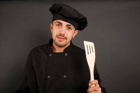 Spanish cook wearing black hat and holding a wooden spoon