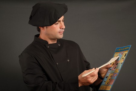 Spanish cook wearing black hat showing a diet board