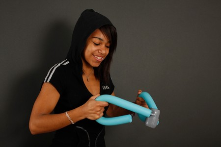 Young girl wearing black hat, using a thigh master in studio