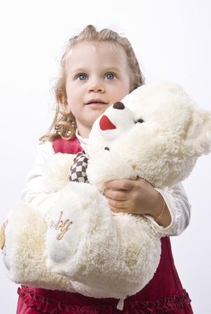 Niña de cabello rubio con ojos azules sosteniendo un oso de peluche