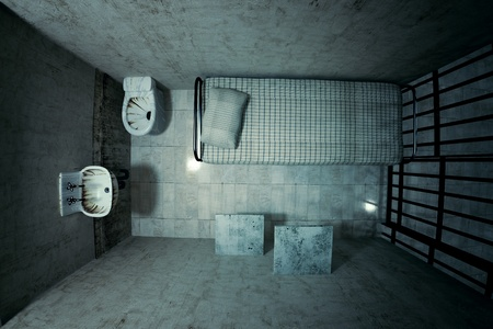 Top view of locked old prison cell for one person with bed, sink, toilet and chair. Dark atmosphere.