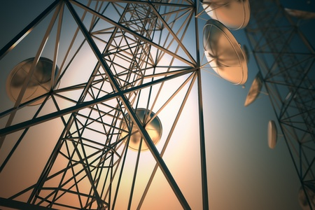 Two tall telecommunication towers with antennas in twilight sky. Close up.