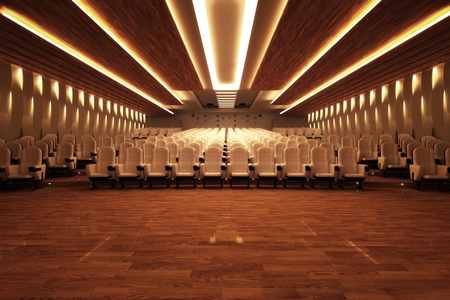 Front shot of a large empty cinema with comfortable white leather seats and a wooden floor.