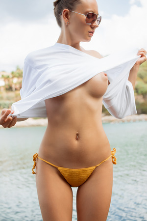 Photo pour Beautiful young female in knitted panties taking off white blouse while standing near water on resort - image libre de droit