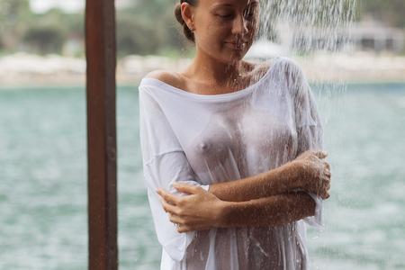 Photo pour Crop woman in wet blouse avoiding water splash - image libre de droit