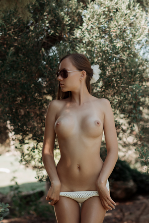 Photo pour Attractive young lady with naked boobies taking off knitted panties while standing in garden - image libre de droit
