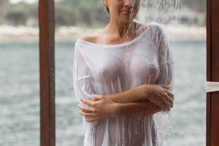 Attractive young female in wet blouse looking away while standing near splashing clean water in resort