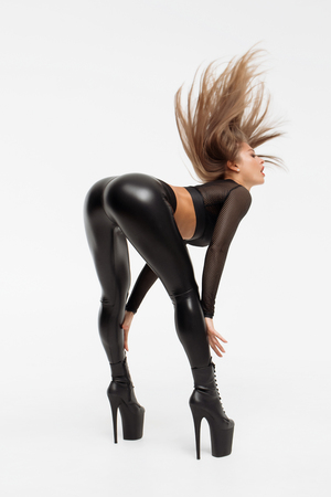 Alluring woman wearing high heels with black leather pants bending over and posing provocatively