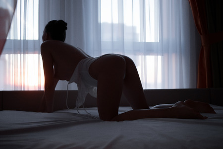 Foto per Back view of attractive slim nude lady in underwear posing on bed near window in dark room - Immagine Royalty Free