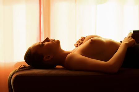 Foto de Beautiful slim sexual nude woman in bodysuit with closed eyes lying on settee in room - Imagen libre de derechos