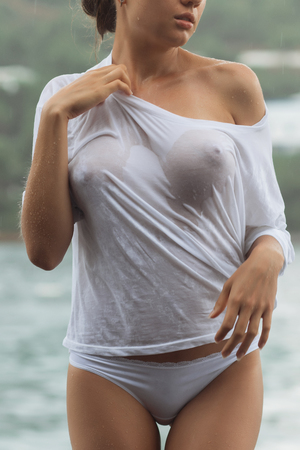 Photo pour Attractive young female in while blouse and panties embracing herself and keeping eyes closed while standing near water on windy day - image libre de droit