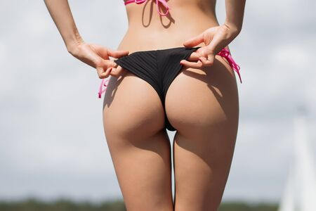 Photo pour Back view of slim sexy woman in sunglasses taking off swimsuit panties on background of yacht - image libre de droit